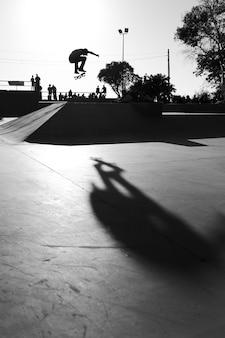 Foto em tons de cinza de um homem fazendo manobras com um skate