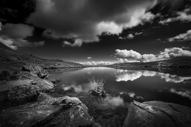 Foto em tons de cinza de um lago cercado por montanhas sob um céu cheio de nuvens
