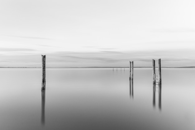 Foto em tons de cinza de um píer de madeira perto do mar sob um lindo céu nublado