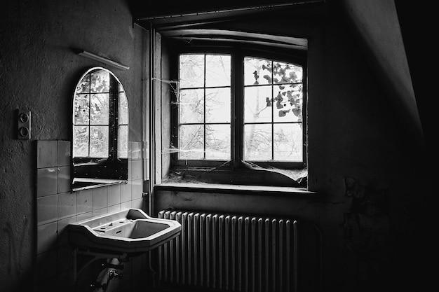 Foto em tons de cinza de um quarto abandonado com uma pia, um espelho e teias de aranha por toda a janela