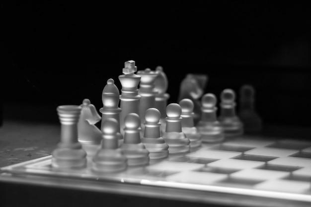 Foto em tons de cinza de um tabuleiro de xadrez de vidro