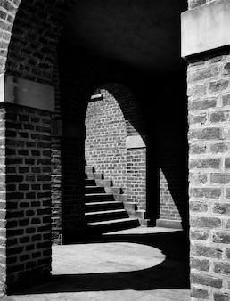 Foto em tons de cinza de uma escada com uma parede de tijolos