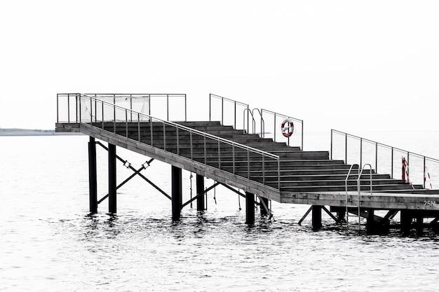 Foto em tons de cinza de uma escada para um local de pé sobre o mar