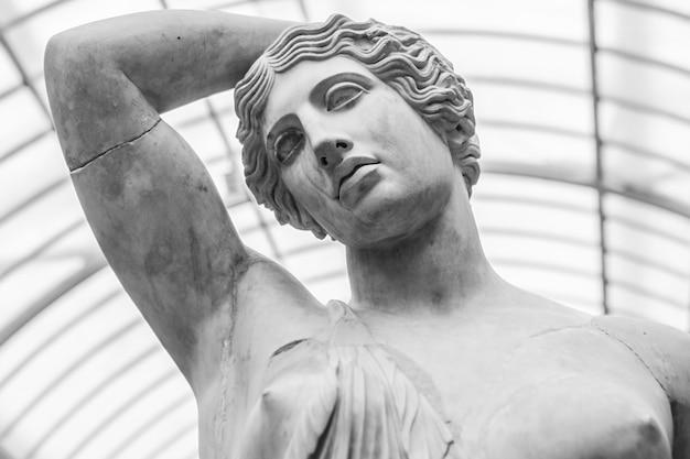 Foto em tons de cinza de uma estátua de mármore de uma mulher sob as luzes