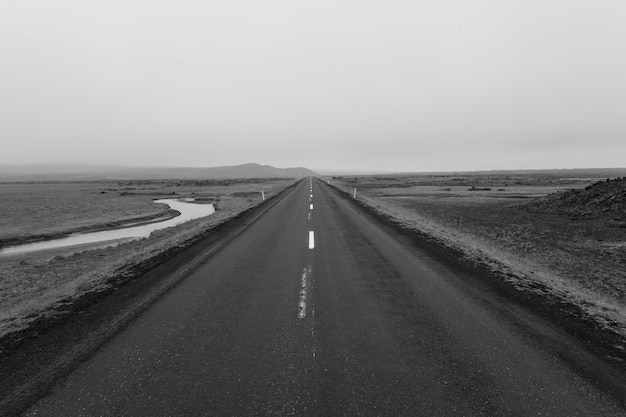 Foto em tons de cinza de uma estrada no meio de um campo vazio sob um céu nublado
