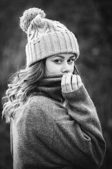 Foto em tons de cinza de uma jovem mulher branca vestindo um suéter cinza e um chapéu de inverno - conceito de inverno