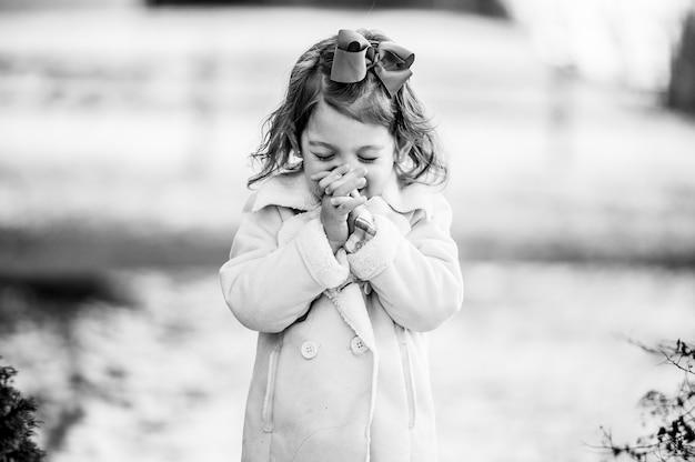Foto em tons de cinza de uma linda garota fazendo um pedido com os olhos fechados