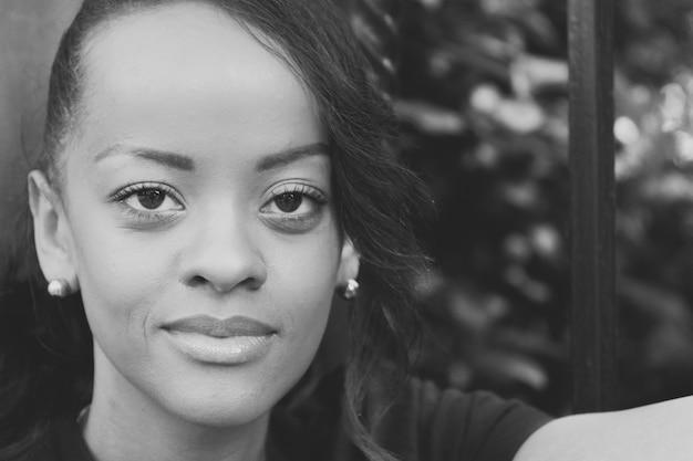 Foto em tons de cinza de uma mulher afro-americana sorridente