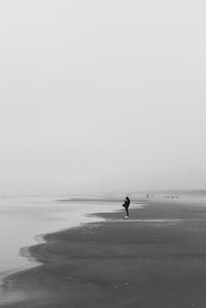 Foto em tons de cinza de uma pessoa solitária caminhando na praia sob nuvens escuras