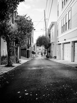 Foto em tons de cinza de uma rua vazia entre casas com algumas árvores