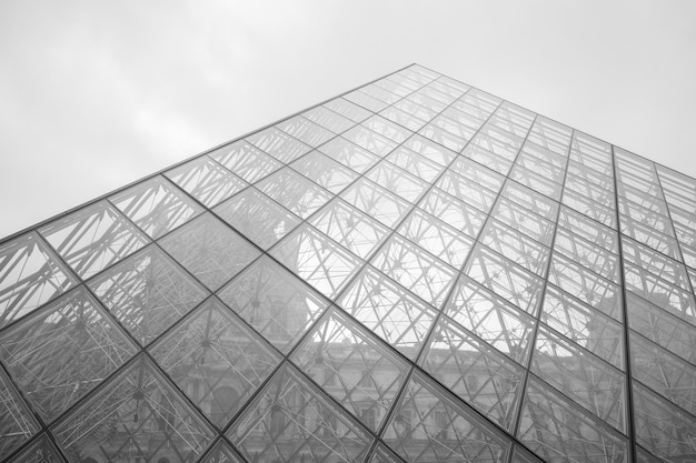 Foto em tons de cinza do museu do louvre sob um céu nublado em paris, frança