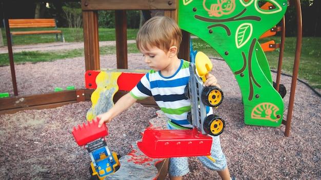 Foto em tons de um lindo garotinho brincando com um caminhão de brinquedo e um trailer no parquinho do parque