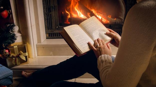 Foto em tons de uma mulher lendo um livro ao lado da lareira e uma lareira acesa