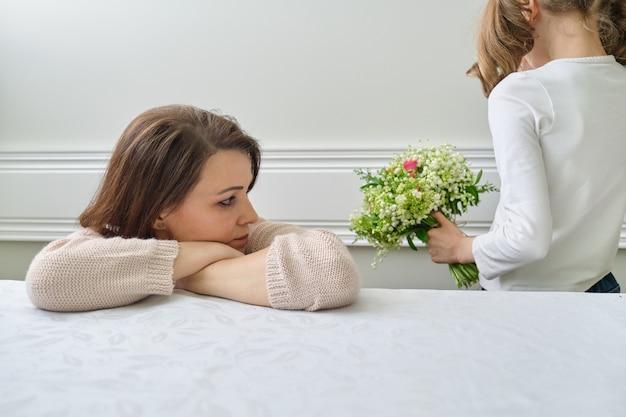 Foto emocional de mãe e filha, menina com buquê de flores cobrindo o rosto