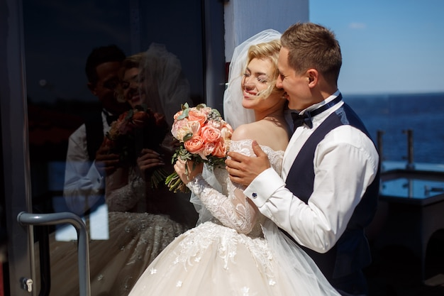 Foto emocional de um casal apaixonado no dia do casamento. sorrindo recém-casados. fotografia de casamento. feliz noiva e noivo huggings ao ar livre