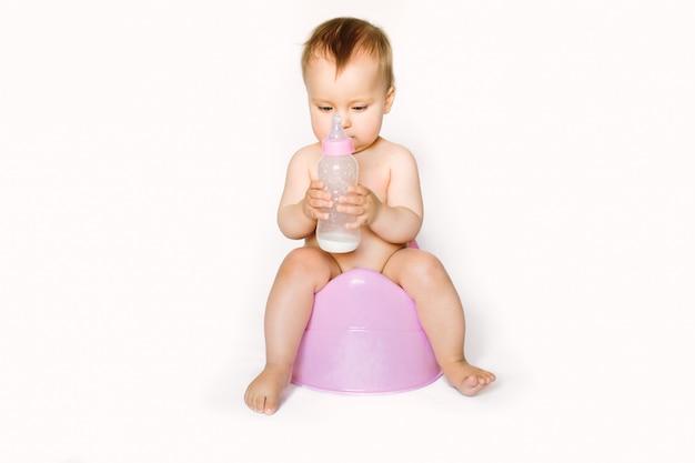 Foto encantadora de menina bonito, segurando uma garrafa com leite do bebê e sentado em um penico rosa. isolado no fundo branco