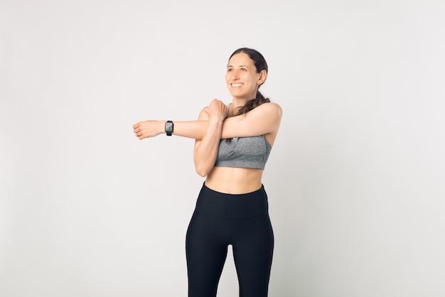Foto encantadora jovem esporte fitness mulher fazendo alongamento sobre fundo branco