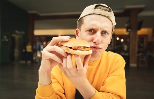 Foto engraçada de um jovem alegre de boné e suéter amarelo sentado em um restaurante fast-food