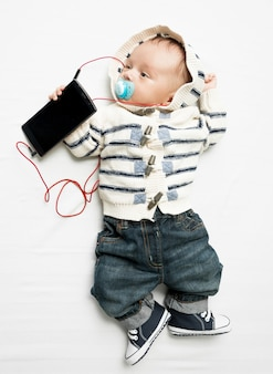 Foto engraçada de um lindo menino ouvindo música no telefone com fones de ouvido