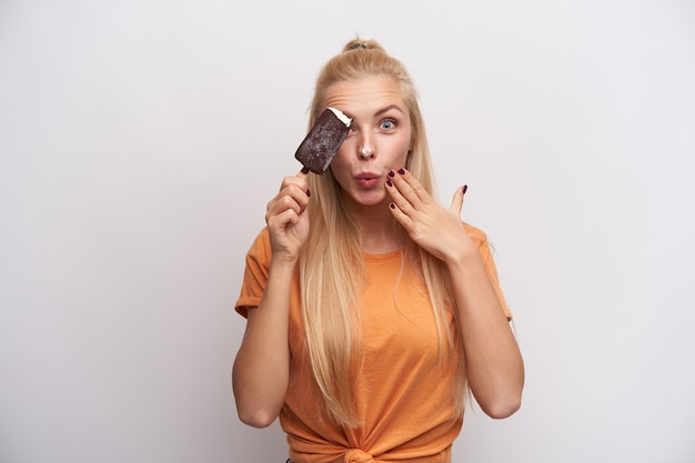 Foto engraçada de uma adorável jovem loira de olhos azuis levantando o sorvete e tocando suavemente seu rosto enquanto olha para a câmera com espanto, em pé contra um fundo branco