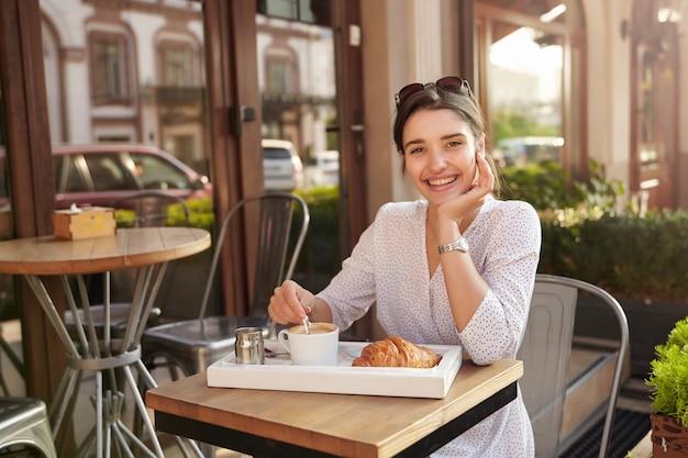 Foto ensolarada de uma jovem alegre adorável mulher de cabelos escuros vestindo bolinhas brancas, sentada à mesa no café da cidade, apoiando o queixo na mão levantada e sorrindo alegremente
