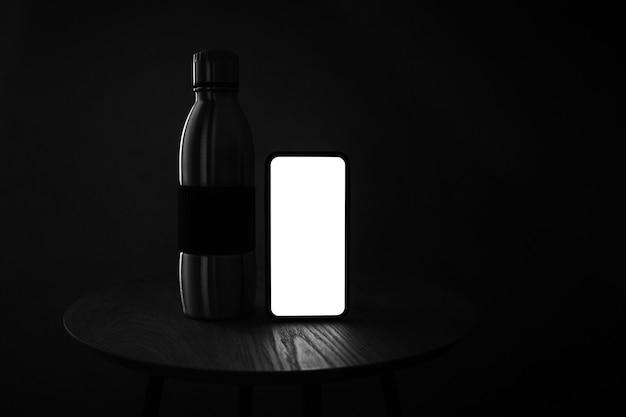 Foto escura em preto e branco de smartphone com tela em branco e garrafa térmica reutilizável de aço na mesa de madeira