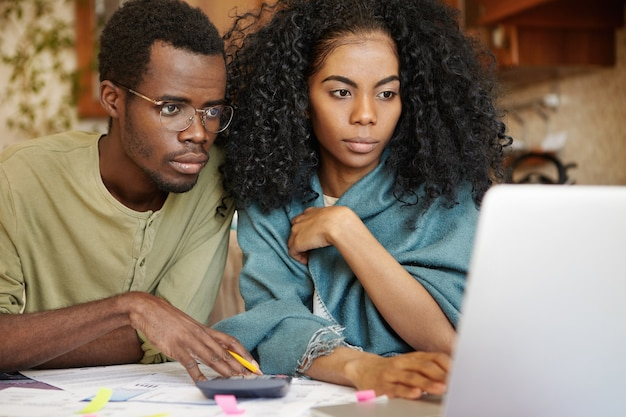 Foto espontânea de close-up de um jovem casal de pele escura sentado em frente a um laptop aberto
