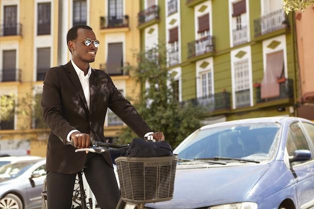 Foto espontânea de trabalhador de escritório afro-americano feliz e ecologicamente consciente de sucesso, usando óculos escuros e terno formal pendulares para trabalhar em bicicleta, em pé com um veículo de duas rodas em ambiente urbano