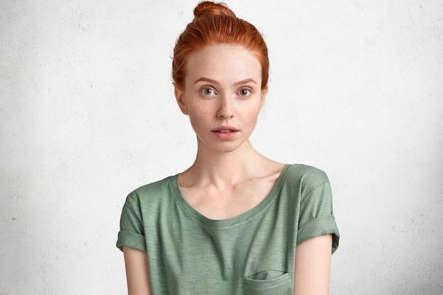 Foto espontânea de uma linda mulher ruiva com pele sardenta saudável, usa uma camiseta casual, olha com confiança para a câmera, posa contra o concreto