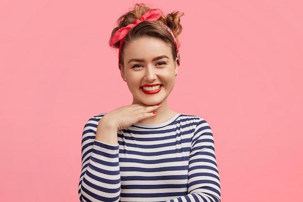Foto espontânea de uma mulher de aparência agradável com maquiagem, tem expressão positiva, mantém a mão sob o queixo, usa suéter listrado e tiara estilosa