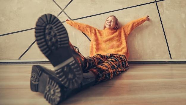 Foto estilizada de uma garota sonhadora, sentada perto de uma parede.