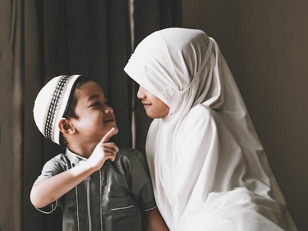 Foto fechada de crianças muçulmanas asiáticas, uma irmã e um irmão em trajes tradicionais muçulmanos