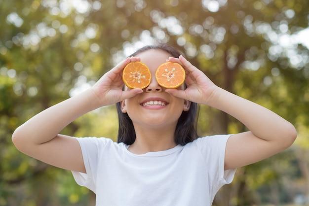 Foto feliz garotinha asiática em pé mostrando os dentes da frente com um grande sorriso. cobrindo os olhos com laranja com folhagem borrada abstrata e verão brilhante.
