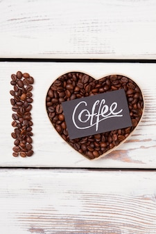 Foto flatlay de grãos de café em forma de coração. eu amo o conceito de café. superfície de madeira branca.
