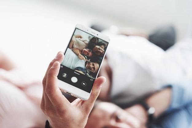 Foto focada do telefone segurando pelo homem tirando uma selfie com amigos que se deitam