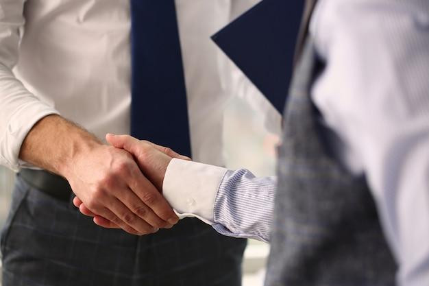 Foto focada em duas pessoas que apertam as mãos