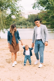 Foto fofa de família de mãos dadas e andando perto de um lago na areia