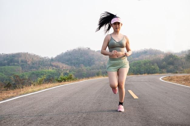 Foto fone view asia jovem sorridente mulher correndo em estrada de asfalto