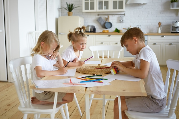 Foto franca de três adoráveis crianças, irmãos de aparência europeia, sentados à mesa da cozinha e fazendo desenhos de família juntos, usando lápis coloridos, concentrando-se em expressões sérias