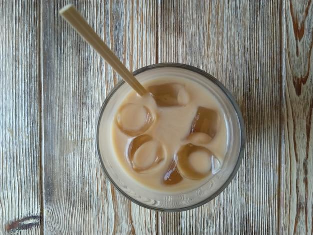 Foto frontal de coquetel de café com tônica e gelo na mesa de madeira branca