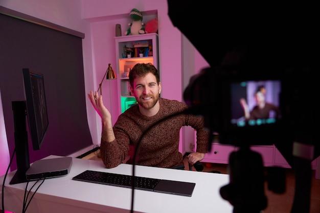 Foto frontal de streamer transmitindo ao vivo com uma câmera profissional
