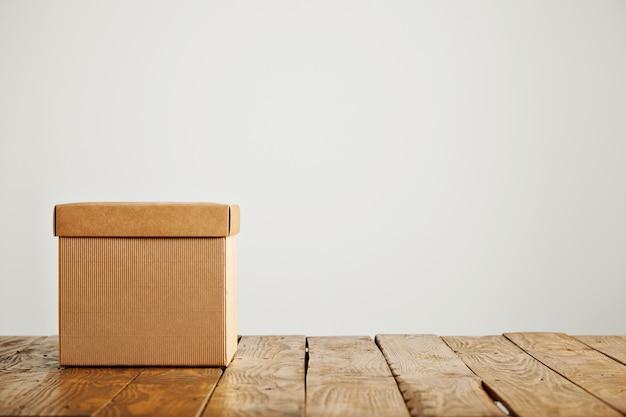 Foto frontal de uma caixa de papelão bege quadrada sem etiqueta com tampa no piso de madeira, isolada no branco