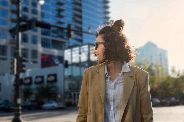 Foto frontal de uma mulher latina de perfil com óculos escuros sorrindo em uma cidade dos estados unidos, copie o espaço
