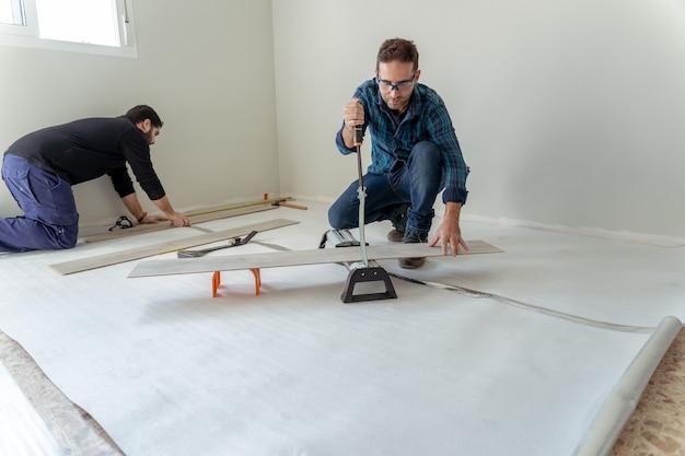 Foto geral de dois homens trabalhando na instalação de um piso de madeira laminado