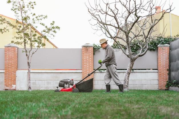 Foto geral de um homem com um chapéu de palha cortando a grama com um cortador de grama no jardim de sua casa