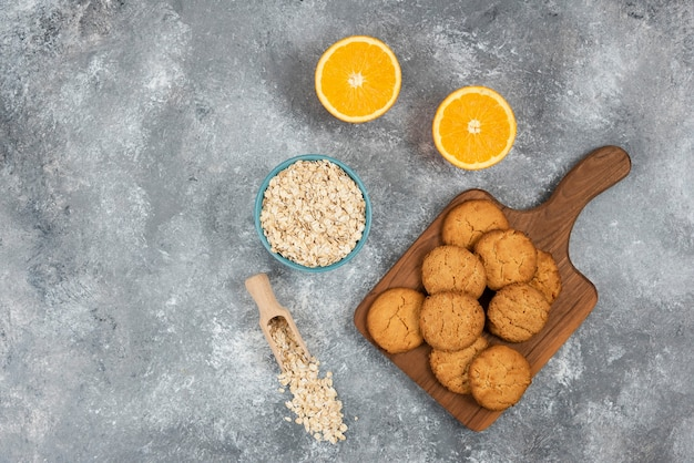 Foto grande angular de biscoitos caseiros em uma placa de madeira e mingau de aveia com laranjas sobre a superfície cinza
