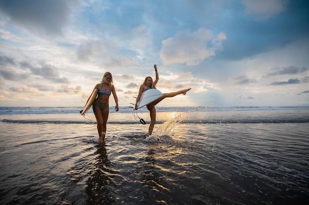 Foto grande angular de duas mulheres em pé na praia durante o pôr do sol
