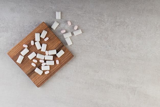 Foto grande angular de gomas brancas em uma placa de madeira sobre uma superfície cinza