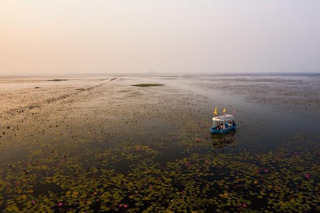 Foto grande angular de um barco no lago de lótus, na tailândia
