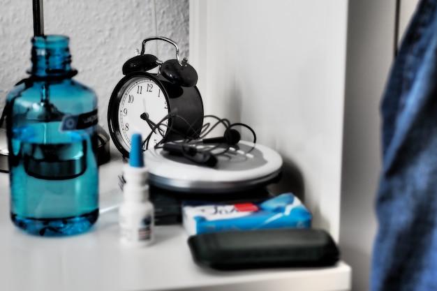 Foto grande angular de um relógio, garrafa e outros objetos em uma mesa